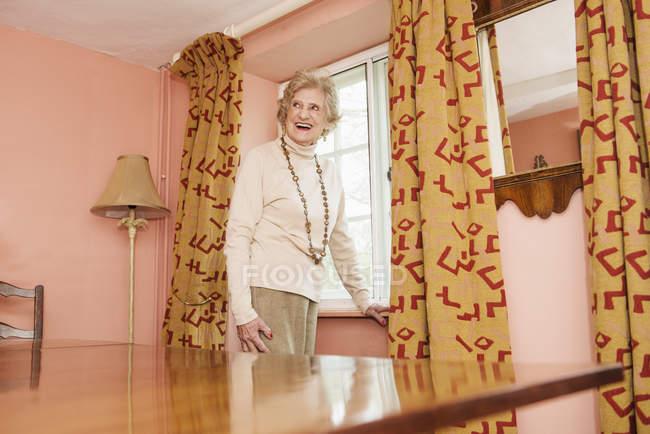 Портрет старшої жінки, що стоїть на вінтажному домашньому інтер'єрі — стокове фото