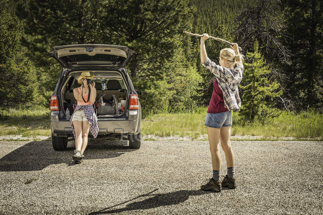 Young woman photographing teenage girl hiker holding up walking stick on rural road, Red Lodge, Montana, USA — Stock Photo