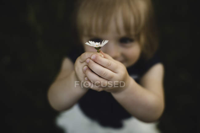 Girl holding up daisy flower smiling — Stock Photo