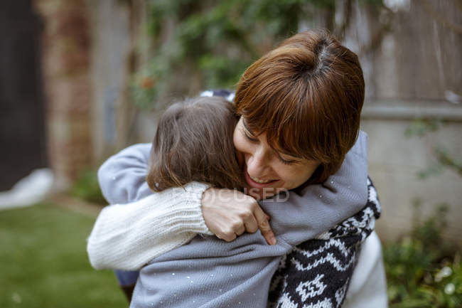 Mother and daughter hugging each other outdoors — Stock Photo