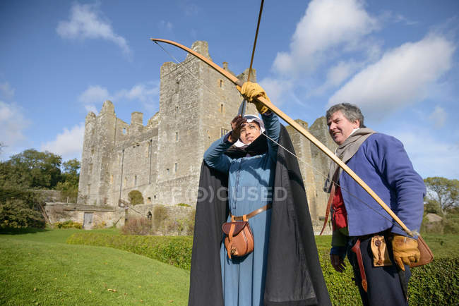 Uomo che insegna storia tiro con l'arco studentesco in abito d'epoca fuori dal Castello di Bolton, edificio classificato di Grado 1 del XIV secolo, monumento antico pianificato — Foto stock
