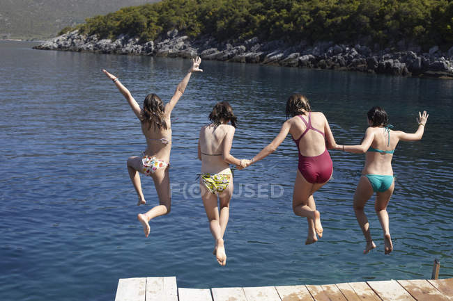Four teenage girls jumping from pier into sea water — Stock Photo