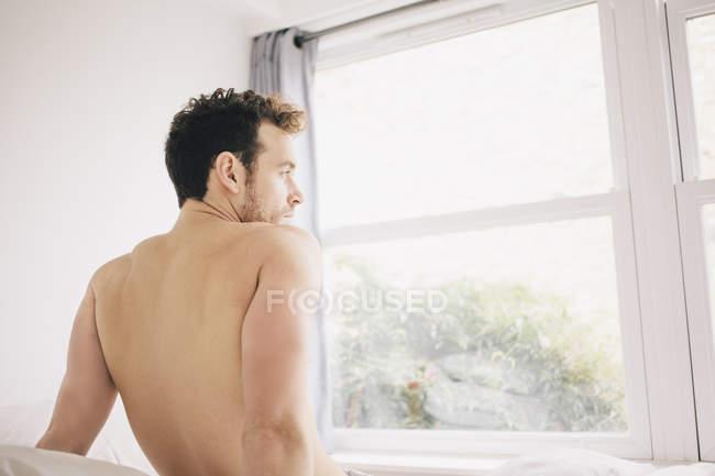 Junger Mann, Blick aus dem Schlafzimmerfenster Morgen — Stockfoto