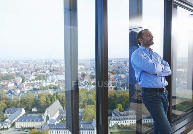 Worried businessman leaning against office window with Brussels cityscape, Belgium — Stock Photo