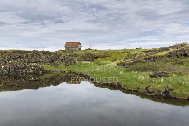 Vista distante da cabana e do fiorde, Hvalfjordur, Islândia — Fotografia de Stock