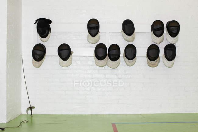 Esgrima máscaras penduradas na parede ao lado da espada — Fotografia de Stock