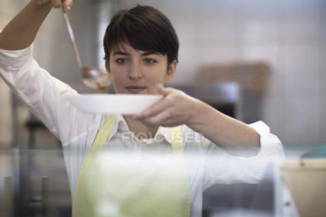 Jeune femme spooning aliments dans le bol dans la boutique de restauration rapide — Photo de stock