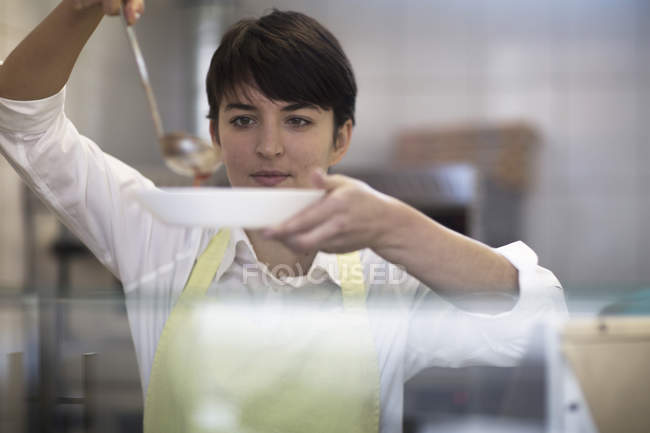 Young woman spooning food into bowl in fast food shop — Stock Photo