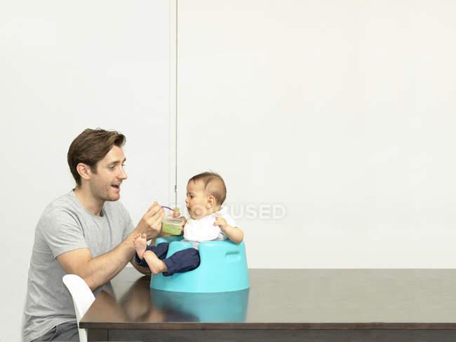 Père nourrissant bébé garçon dans le siège bébé — Photo de stock