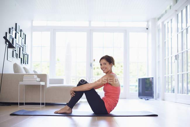 Портрет женщины среднего возраста на коврике для йоги в гостиной — стоковое фото