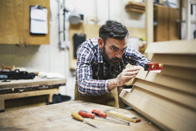 Mature craftsman using spirit level in pipe organ workshop — Stock Photo