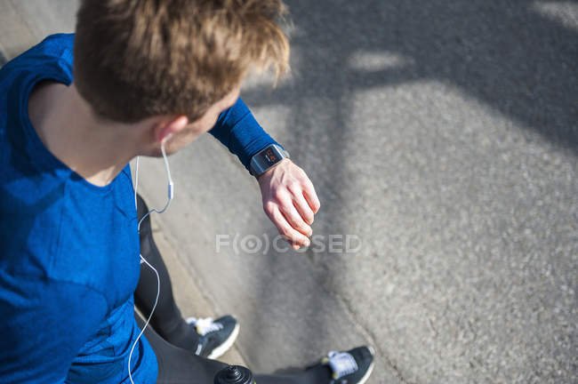 Young man standing outdoors, wearing sports clothing, looking at watch, elevated view — Stock Photo