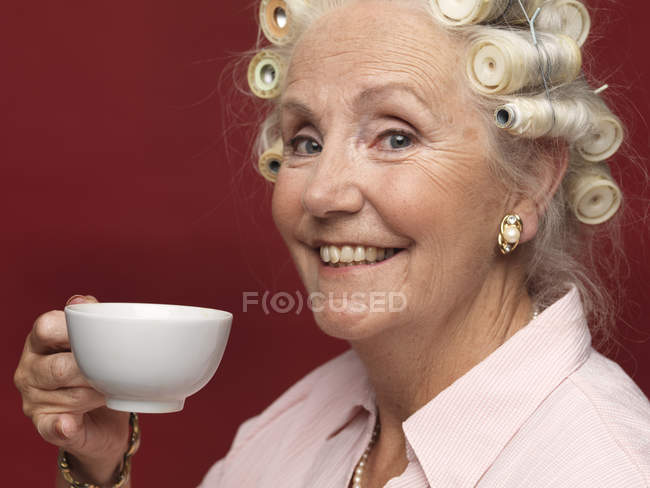Studio portrait of senior woman in hair rollers with cup of tea — Stock Photo