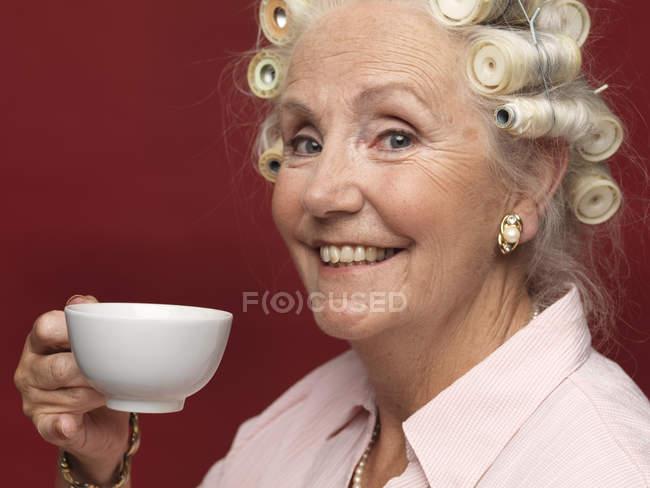 Portrait en studio de haute femme en bigoudis avec tasse de thé — Photo de stock