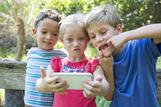Three children taking selfie on smartphone in garden — Stock Photo