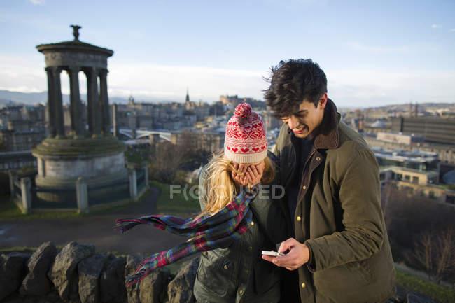 Um jovem casal se fotografa em Calton Hill com o fundo da cidade de Edimburgo, capital da Escócia — Fotografia de Stock