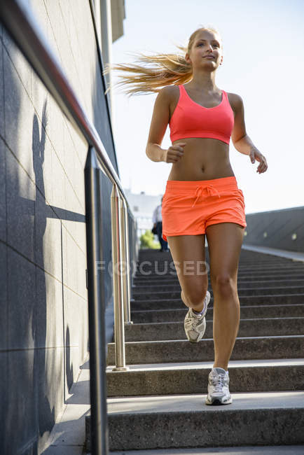 Young female runner moving down city stairway — Stock Photo