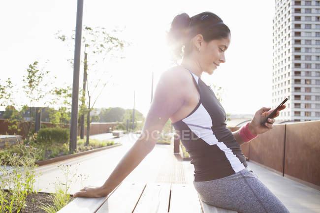 Обучение женщин, сидящих на городском пешеходном мосту и читающих смс-ки — стоковое фото