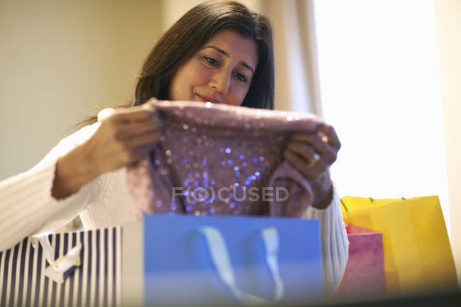 Mature woman removing clothing from shopping bags — Stock Photo