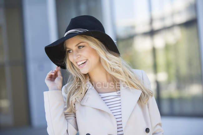 Porträt einer jungen Frau im Freien, mit schwarzem Hut, lächelnd — Stockfoto