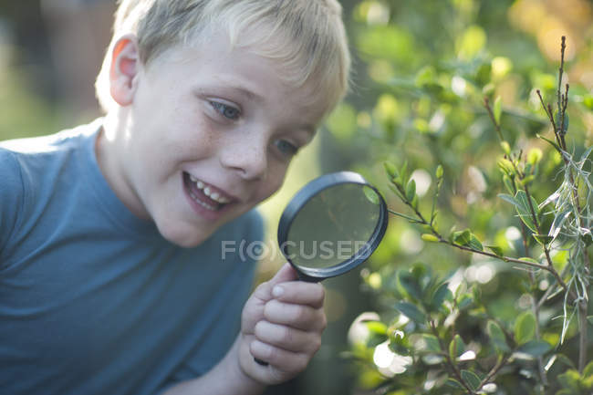 Boy discovering plants with magnifying glass in garden — Stock Photo