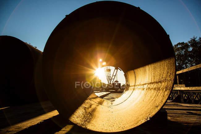 Sunrise through concrete pipe — construction site, united