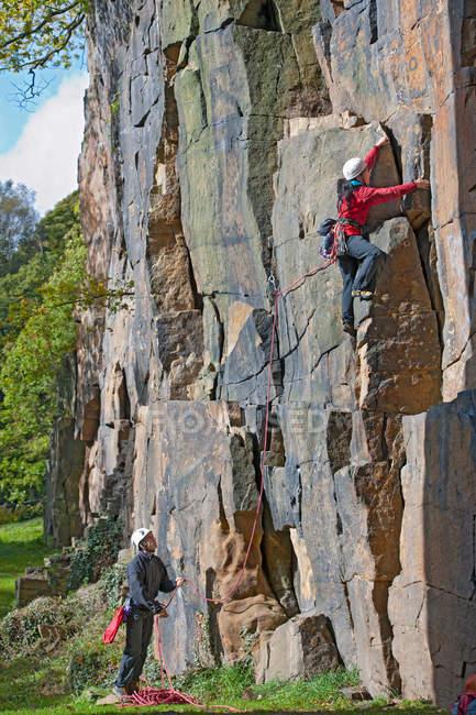Rock climbers scaling steep face — Stock Photo