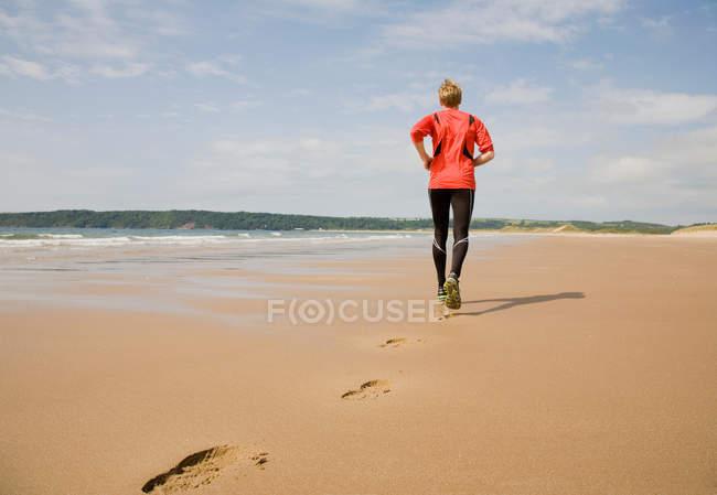 Бегун делает контуры на пляже — стоковое фото