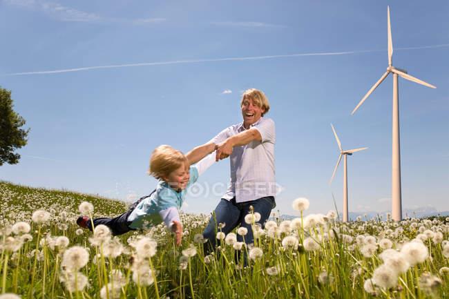 Pai e filho com turbinas eólicas no fundo — Fotografia de Stock