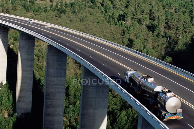 Petroleiro em auto-estrada elevada com floresta verde no fundo — Fotografia de Stock