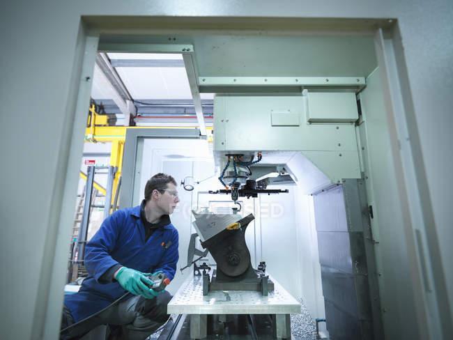 Travailleur utilisant une machine CNC dans une usine de plastique — Photo de stock