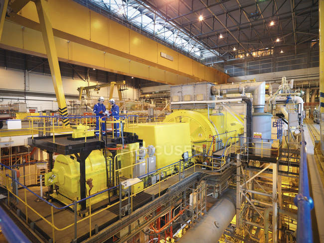 Workers in turbine hall of power station — Stock Photo