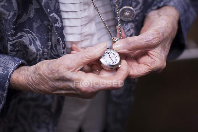 Seniorin, Taschenuhr in der Hand, Mittelteil, Nahaufnahme — Stockfoto