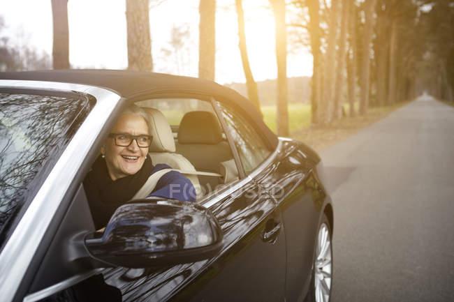 Donna in auto guida sull'albero foderato strada che osserva dalla finestra sorridente — Foto stock