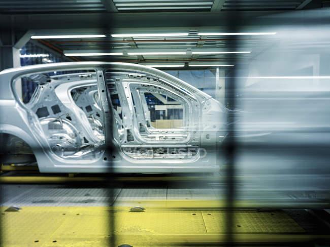 Vista de los coches en la línea de producción en fábrica - foto de stock