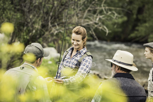Small group of people by river with fishing rod smiling — Stock Photo