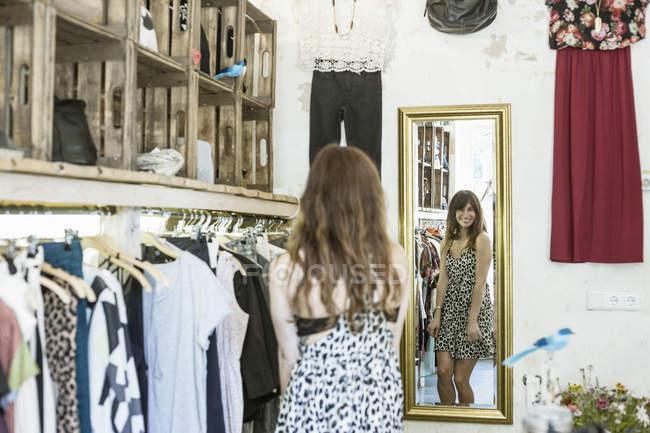 Посередині дорослої жінки, яка одягається перед дзеркалом у вінтажному бутіку. — стокове фото