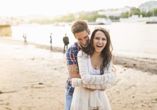 Jeune couple étreindre par rivière — Photo de stock