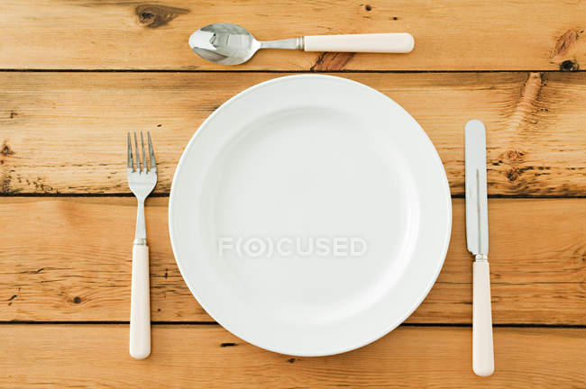 Empty plate with cutlery on wooden table, top view — Stock Photo