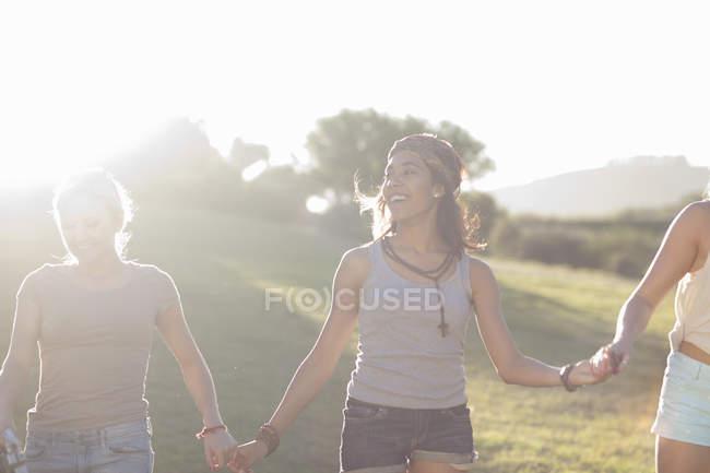 Três jovens amigas de mãos dadas à luz do sol — Fotografia de Stock