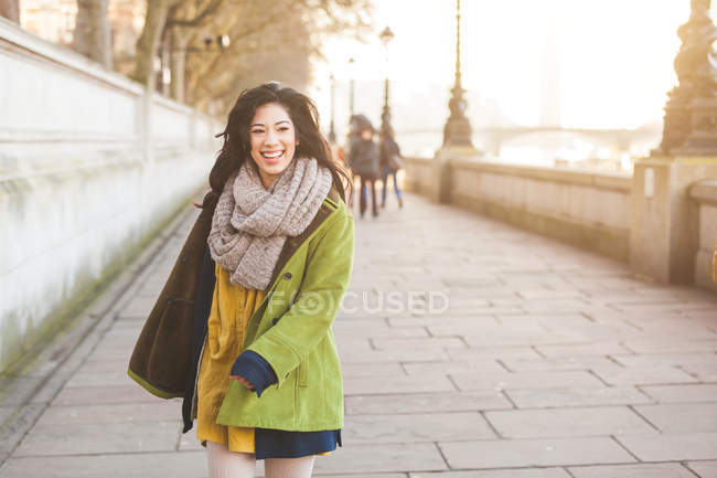 Front view of young woman walking along Thames riverbank looking at camera smiling, London, UK — Stock Photo