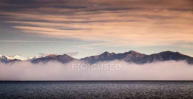 Orilla del mar brumoso y montañas bajo el cielo del atardecer nublado - foto de stock
