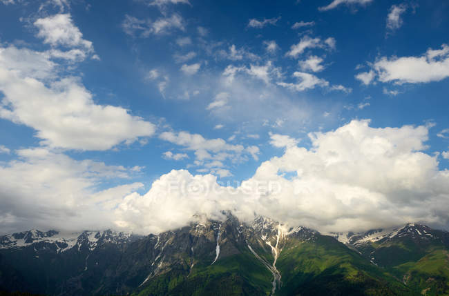 View of distant mountains under blue cloudy sky — Stock Photo