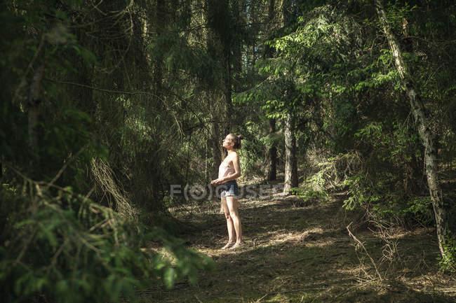 Женщина стоит в лесу и смотрит вверх — стоковое фото