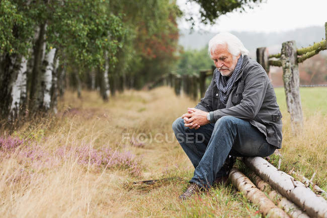 Senior man sitting on log — Stock Photo