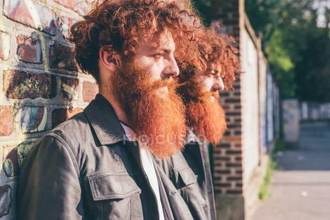 Молодые хипстеры-близнецы с рыжими волосами и бородами, прислонившиеся к кирпичной стене — стоковое фото