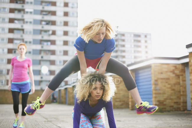 Three women exercising together wearing sports clothing and playing leap frog — Stock Photo