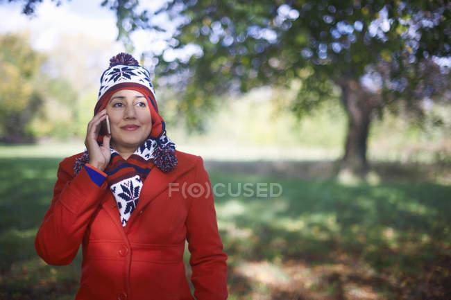 Зрелая женщина пользуется мобильным телефоном в осеннем парке — стоковое фото