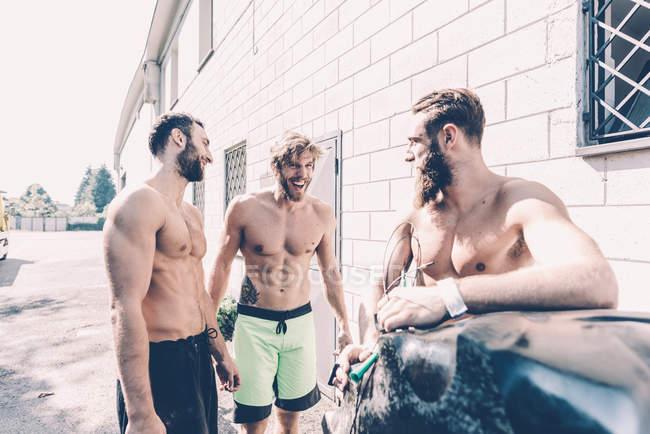 Tre cross trainer di sesso maschile che chattano fuori palestra — Foto stock