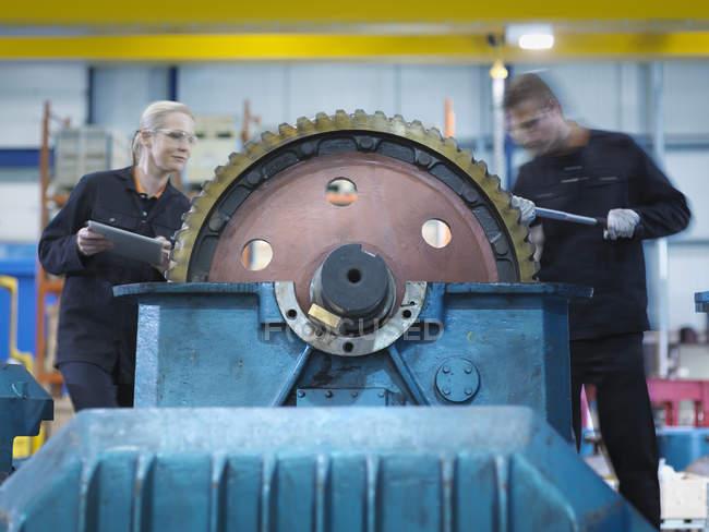 Engineers repairing industrial gearbox in engineering factory — Stock Photo